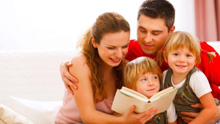 Äiti, isä ja kaksi lasta istuvat sohvalla, äiti lukee lapsille kirjaa
