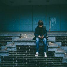 Poika istuu rappusilla ja katsoo puhelinta