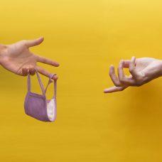 käsi ojentaa kasvomaskia toiselle kädelle