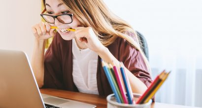 A woman is biting a pencil in front of a laptop