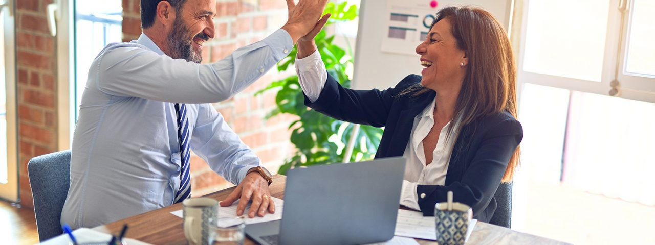 A man and a woman doing high five in an office