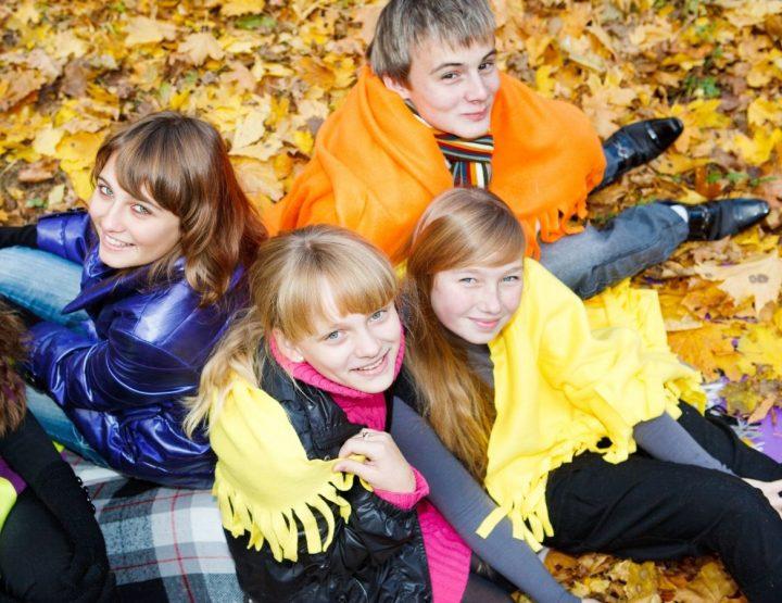 4 nuorta istuu syksyn lehtien peittämällä maalla harteillaan värikkäät viltit