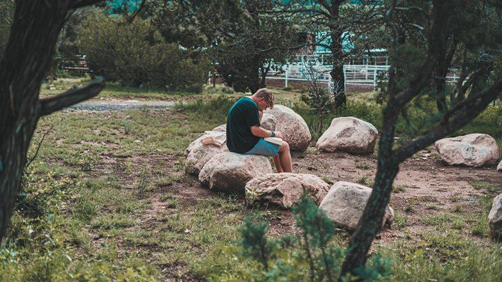 Poika istuu kivellä metsässä